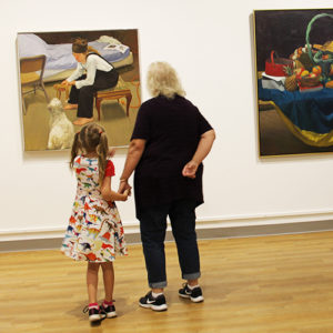 Girl and woman looking at painting